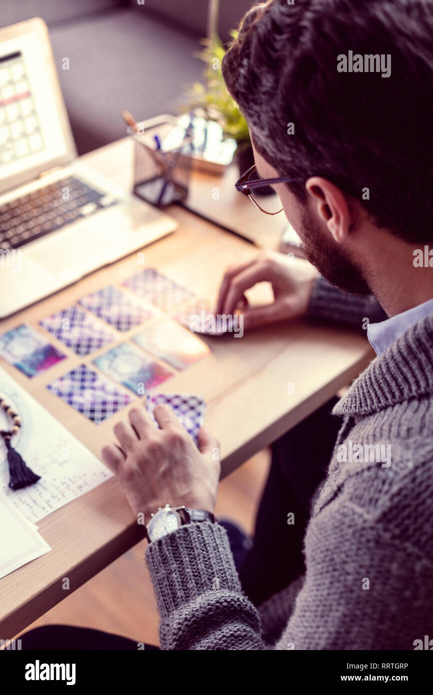 Professional smart male fortuneteller using tarot cards - Stock Image