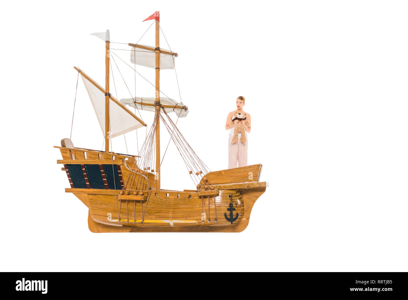 girl in pyjamas holding teddy bear and standing on floating ship model - Stock Image