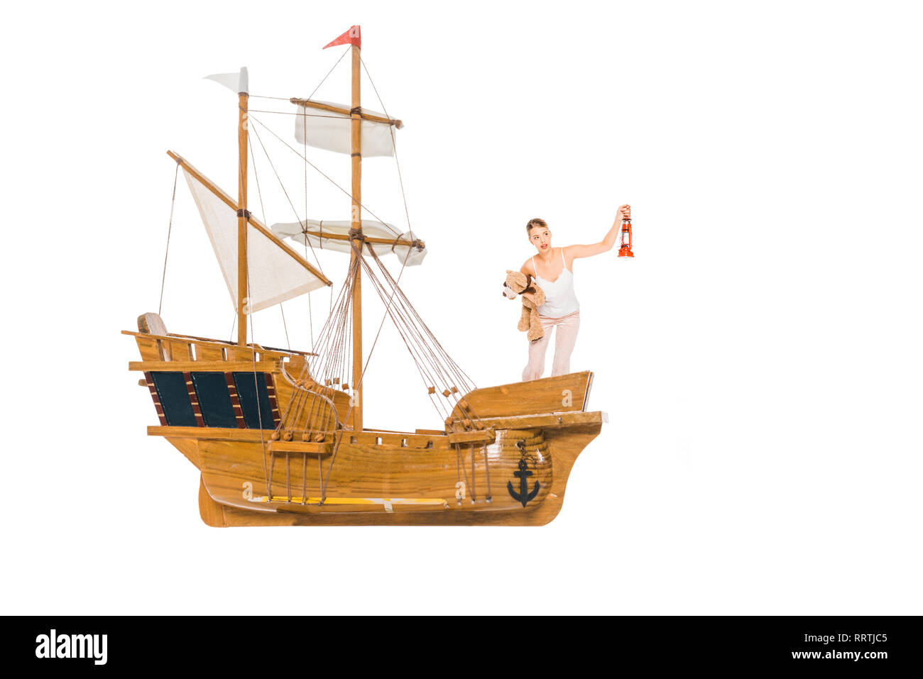 girl in pyjamas holding lantern, teddy bear and standing on floating ship model with copy space - Stock Image