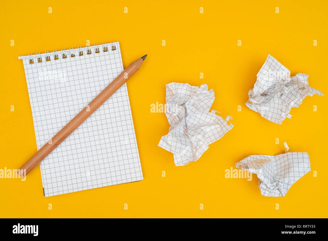Pencil, notebook and crumpled sheets of paper. - Stock Image