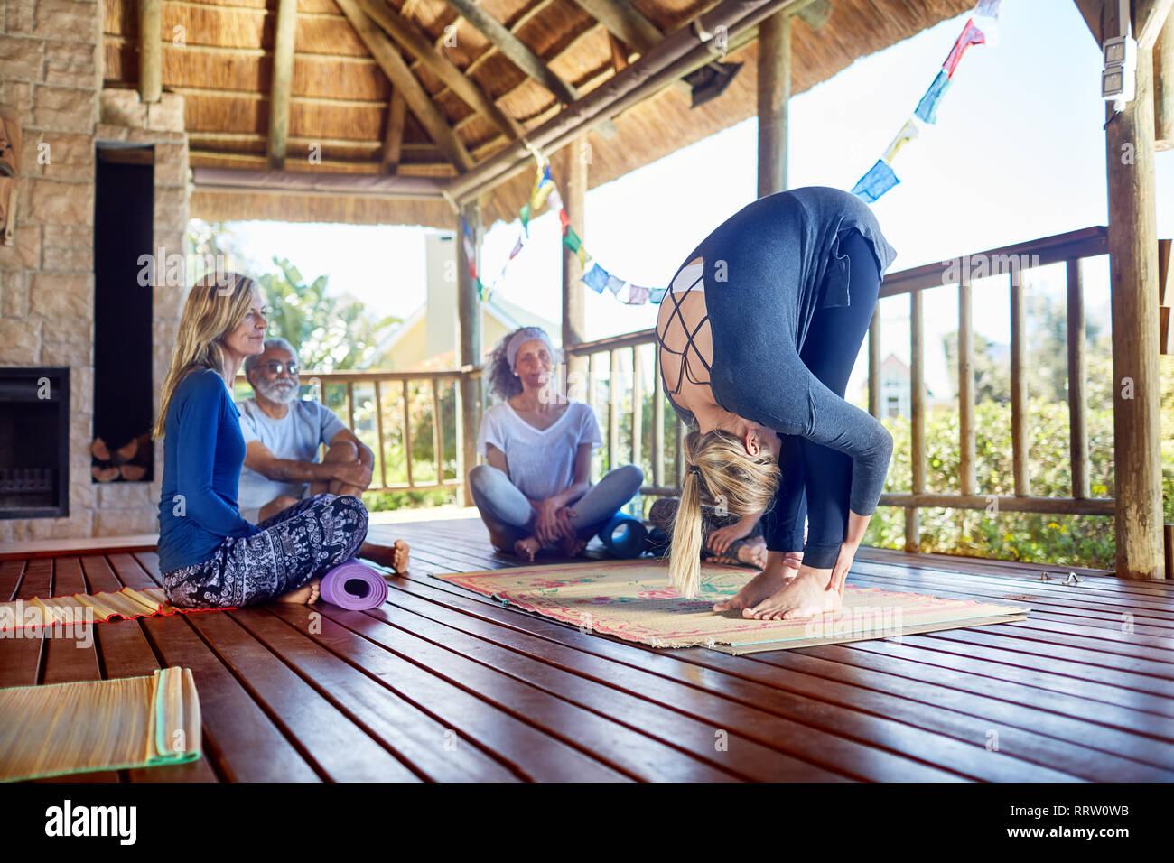 Female yoga instructor demonstrating forward fold in hut during yoga retreat - Stock Image