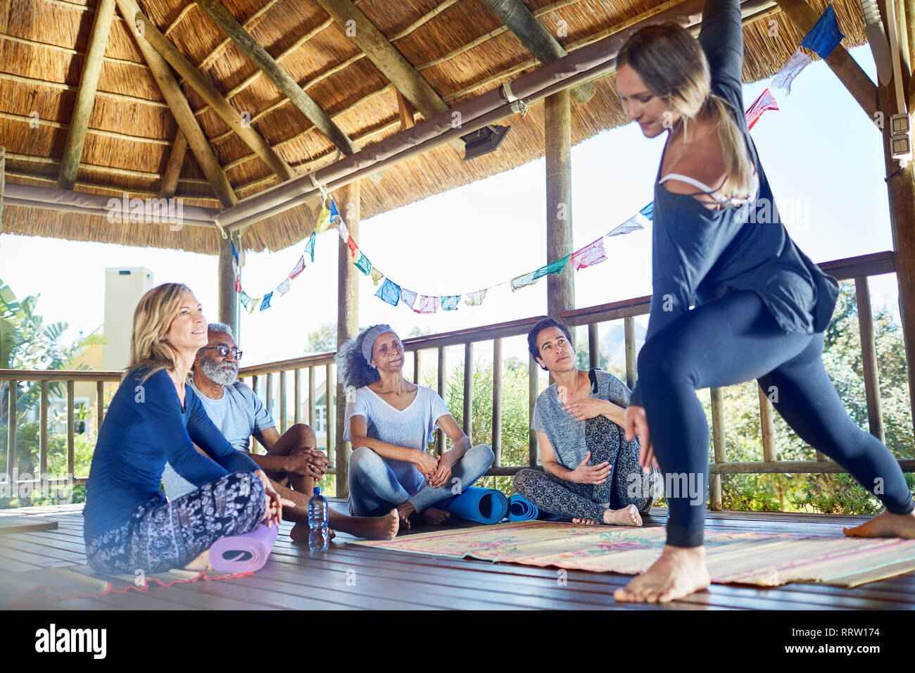 Female instructor demonstrating side angle pose in hut during yoga retreat - Stock Image