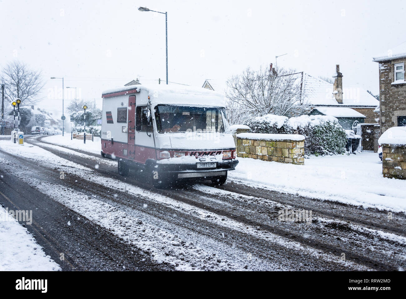 Bradford on Avon, UK, February 1st 2019: A Hymer campervan driving through snowy conditions Campervan out driving in snowy conditions with slush cover Stock Photo
