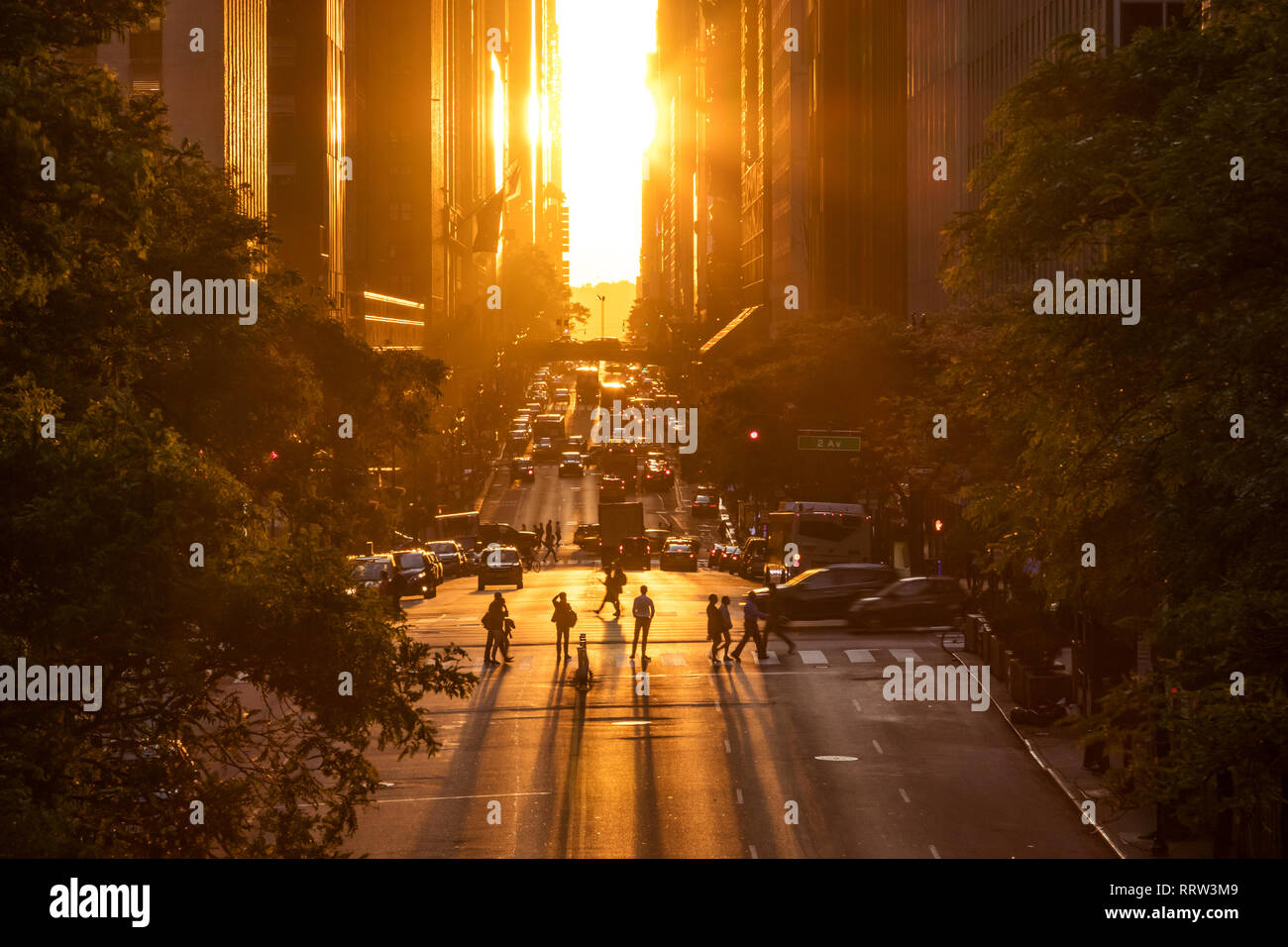 Rays of sunlight shining down on the people and traffic at the intersections along 42nd Street through Midtown Manhattan in New York City Stock Photo