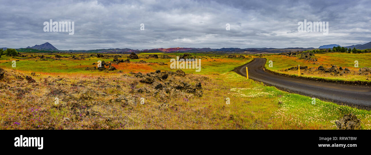 Panoramic view of lava field near lake Myvatn, town Reykjahlid, and volcanoes Hverfjall and Krafla on Iceland - Stock Image