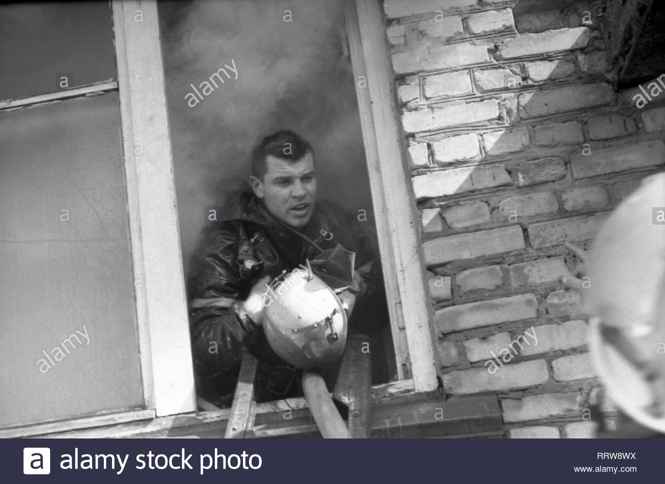 It is fire in the apartment. Firefighter in protective clothing is in the apartment where the fire occurred. The man looks out from open window. He is holding a helmet. Behind him is a dense shroud of smoke. The rescuer receives instructions of the management which is on the street. He saved people... Stock Photo