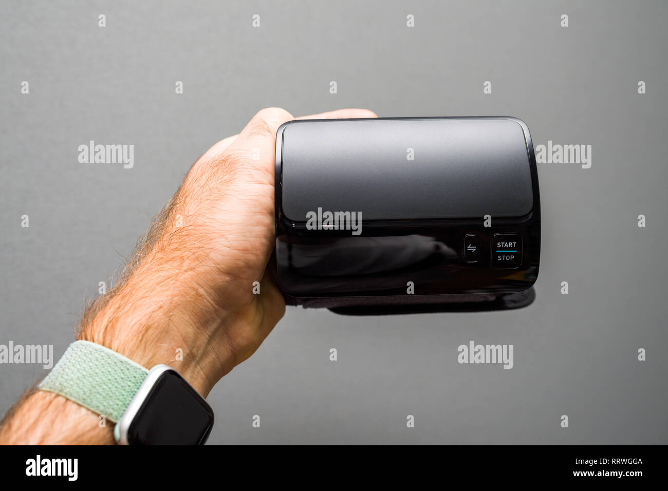 Patient holding against gray background modern electronic internet connected wireless upper arm blood pressure monitor front view  - Stock Image