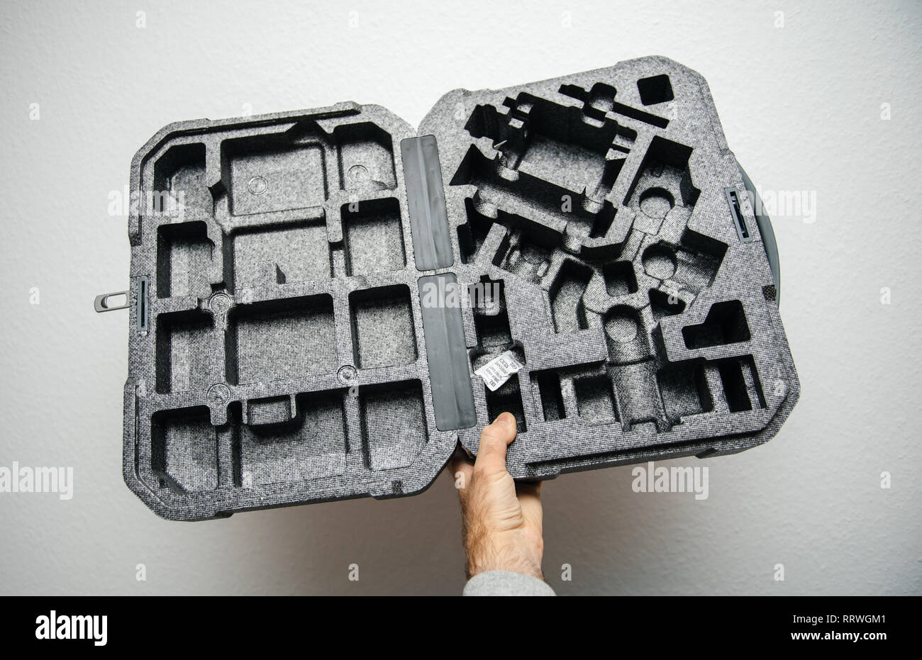 PARIS, FRANCE - NOV 22, 2018: Man hand holding against white background new DJI Ronin S superior 3-axis stabilization system empty packaging foam box - Stock Image