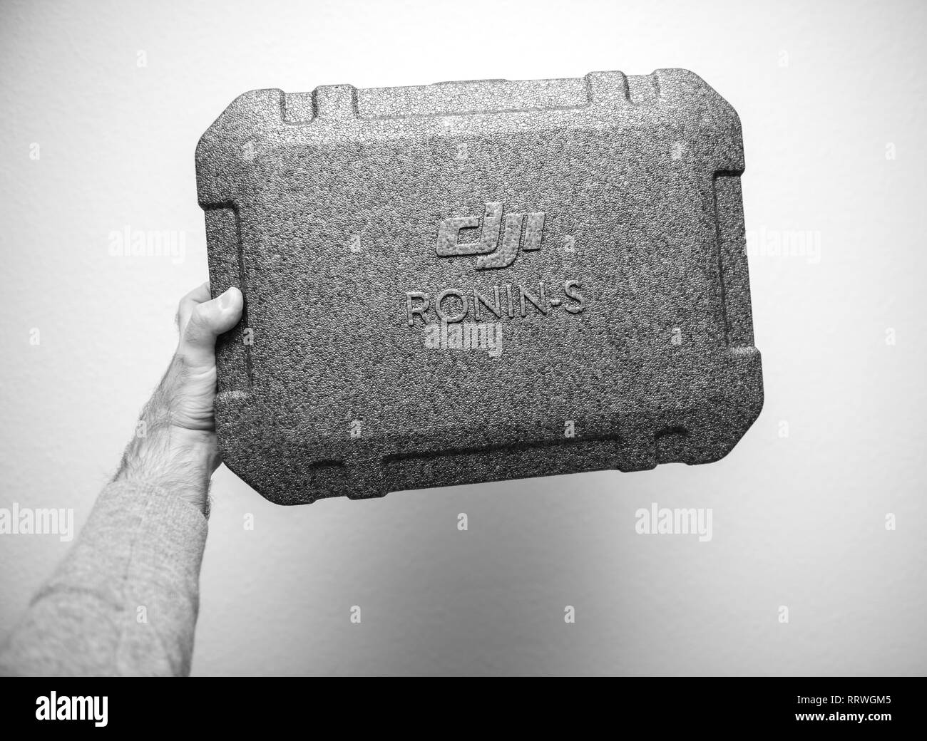 PARIS, FRANCE - NOV 22, 2018: Man hand holding against white background new DJI Ronin S superior 3-axis stabilization system for DSLR and mirrorless camera packaging box - black and white - Stock Image