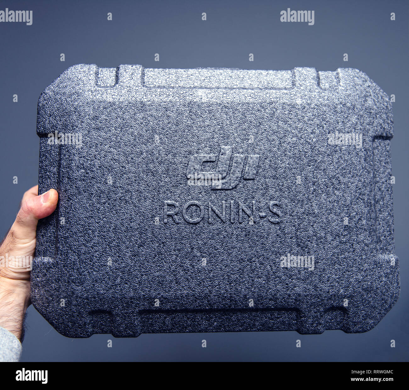 PARIS, FRANCE - NOV 22, 2018: Man hand holding against gray studio background new DJI Ronin S superior 3-axis stabilization system for DSLR and mirrorless camera packaging box - Stock Image