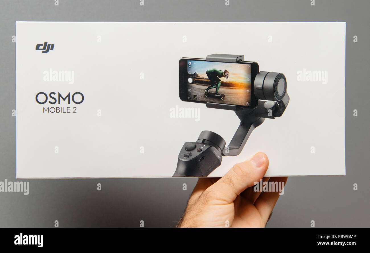 PARIS, FRANCE - NOV 22, 2018: Man hand holding against gray background new DJI Osmo Mobile 2 Smartphone Gimbal manufactured by the SZ DJI Technology Co., Ltd company - Stock Image