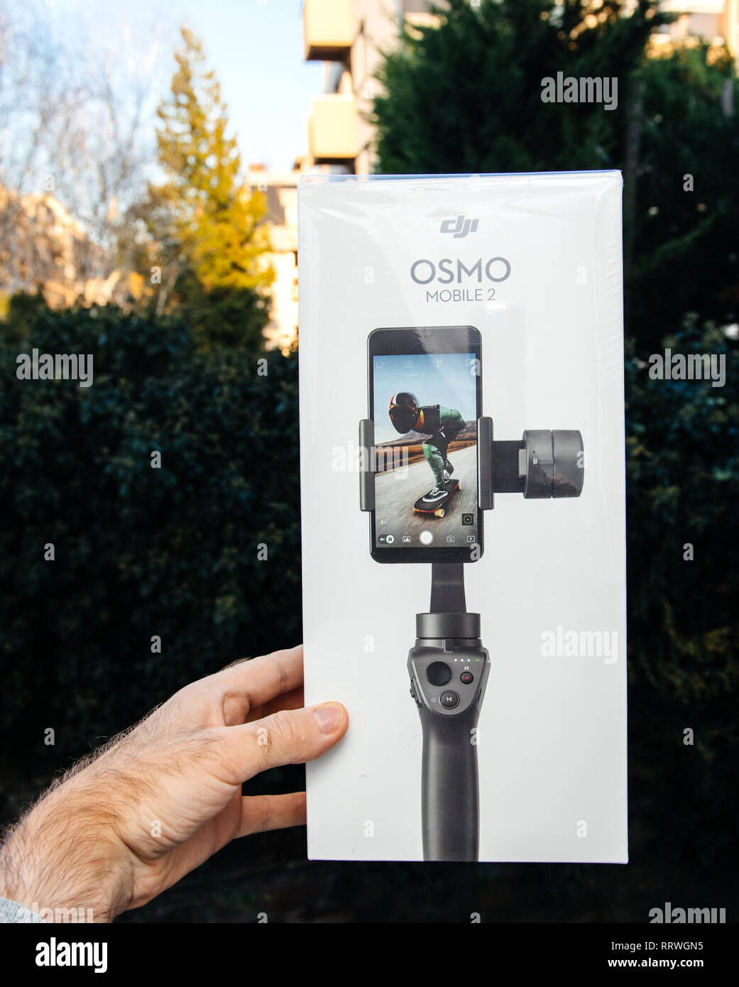 PARIS, FRANCE - NOV 22, 2018: Man hand holding in outdoor background new DJI Osmo Mobile 2 Smartphone Gimbal manufactured by the SZ DJI Technology Co., Ltd company vertical packaging - Stock Image