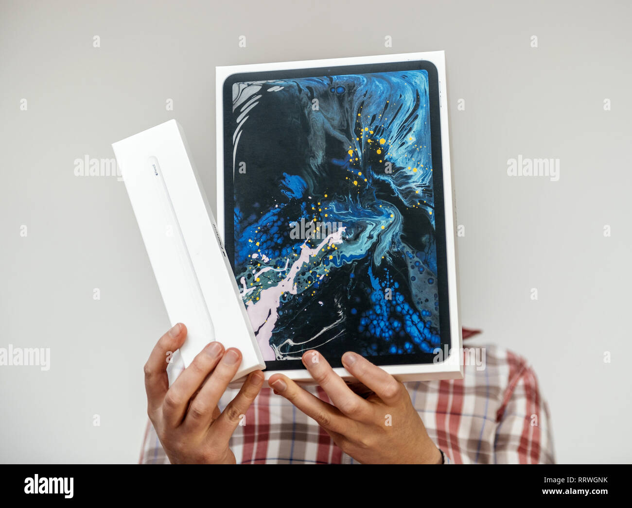 PARIS, FRANCE - DEC 2, 2018: Silhouette holding Apple Computers ipad Pro tablet and Apple Pencil 2 cardboard box - holding the cardboards in front of her face - Stock Image