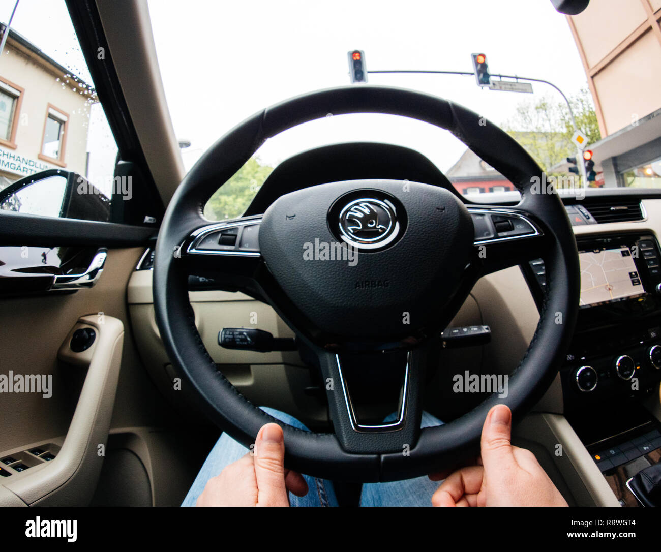 PARIS, FRANCE - MAR 5, 2018: Young woman driving luxury car - view from the interior with ultra-wide lens POV at the Steering wheel with Skoda logotype - Stock Image