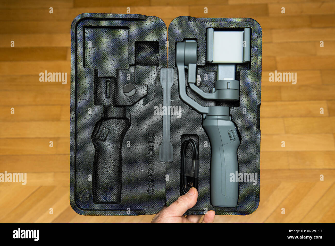 PARIS, FRANCE - NOV 22, 2018: Man unboxing new DJI Osmo Mobile 2 Smartphone Gimbal manufactured by the SZ DJI Technology Co., Ltd company from the foam packaging floor background - Stock Image