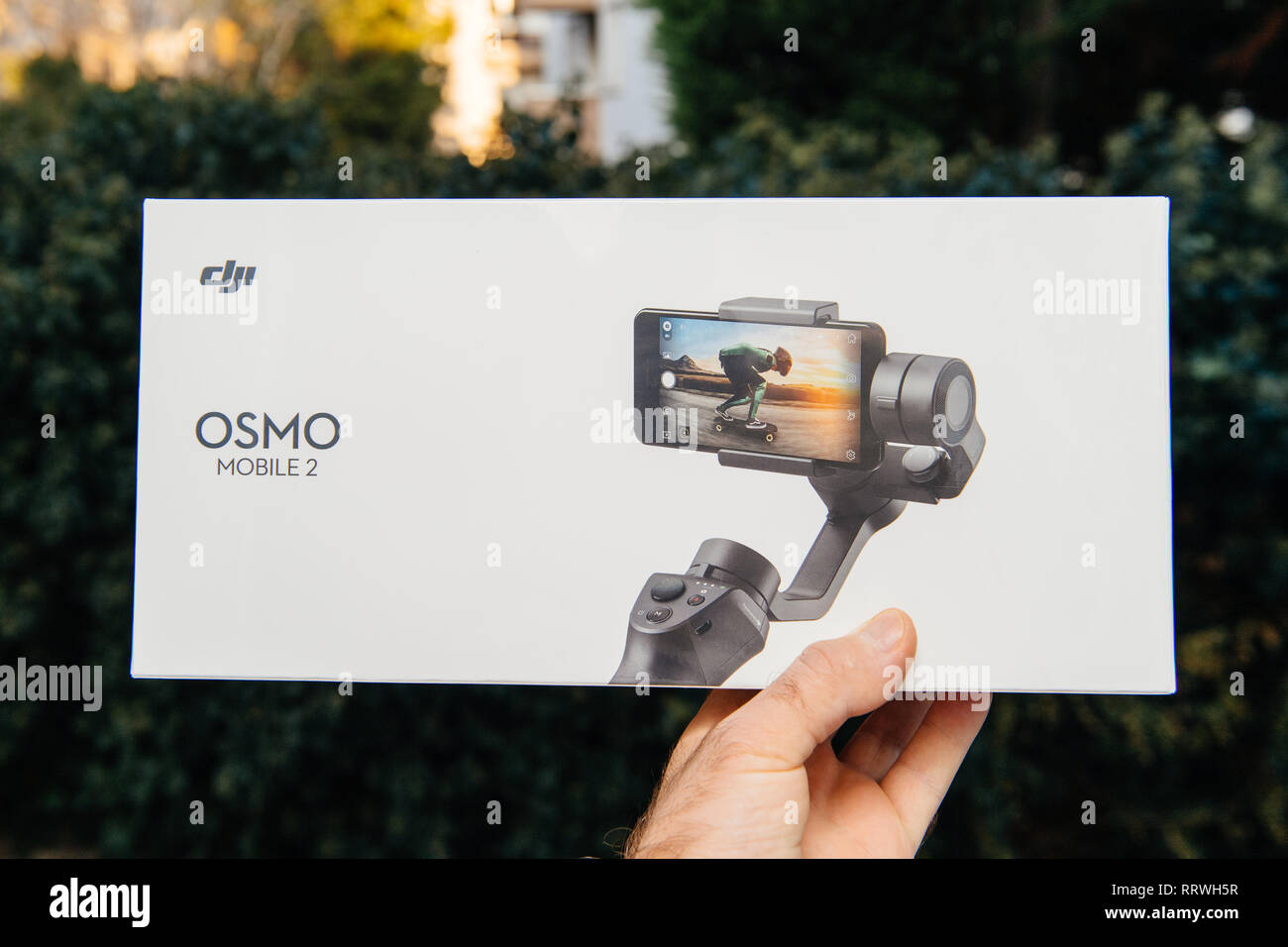 PARIS, FRANCE - NOV 22, 2018: Man hand holding in outdoor background new DJI Osmo Mobile 2 Smartphone Gimbal manufactured by the SZ DJI Technology Co., Ltd company - front packaging featuring device - Stock Image