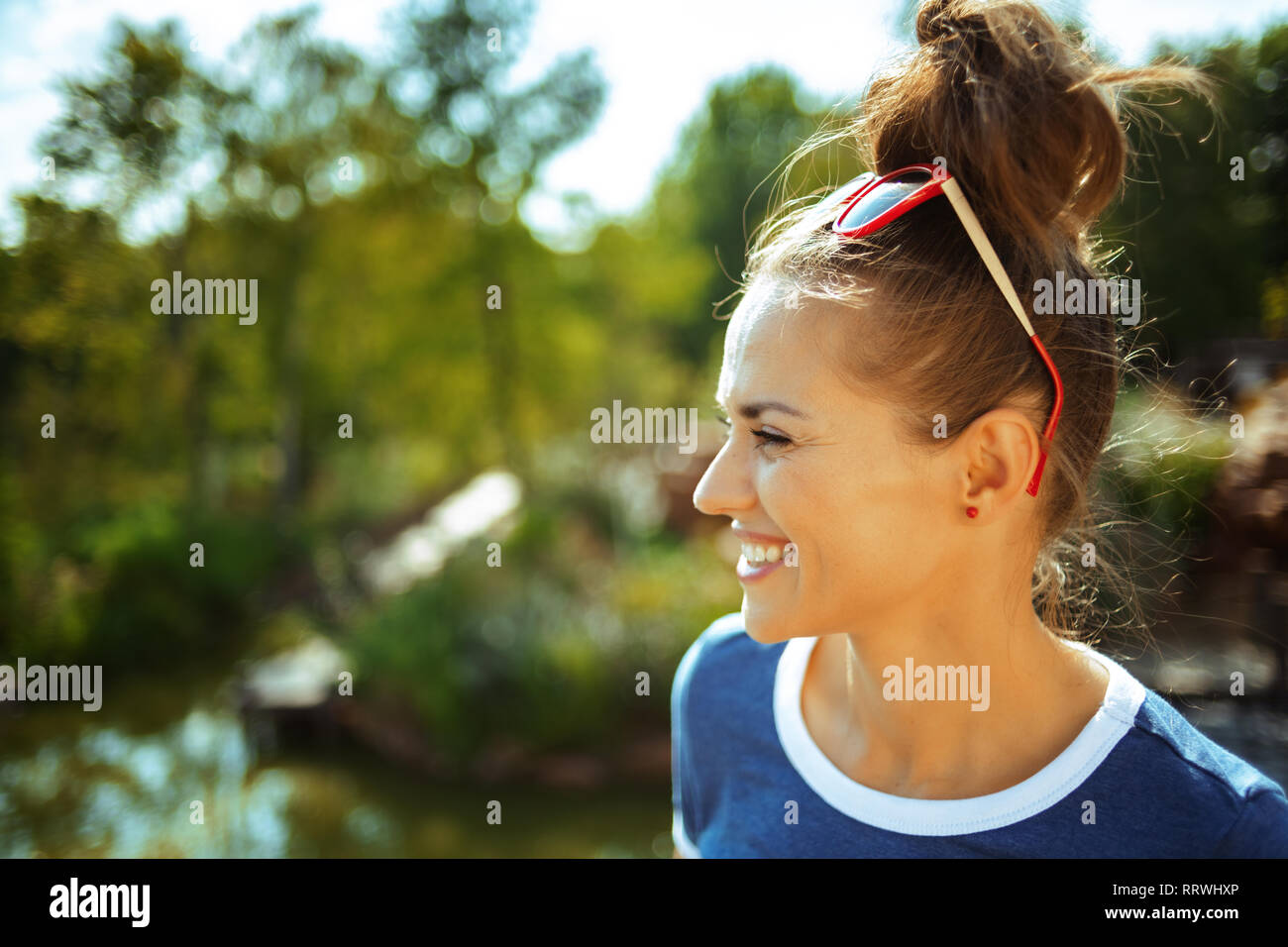 smiling young traveller woman in blue t-shirt on river boat exploring countryside while having river cruise. - Stock Image