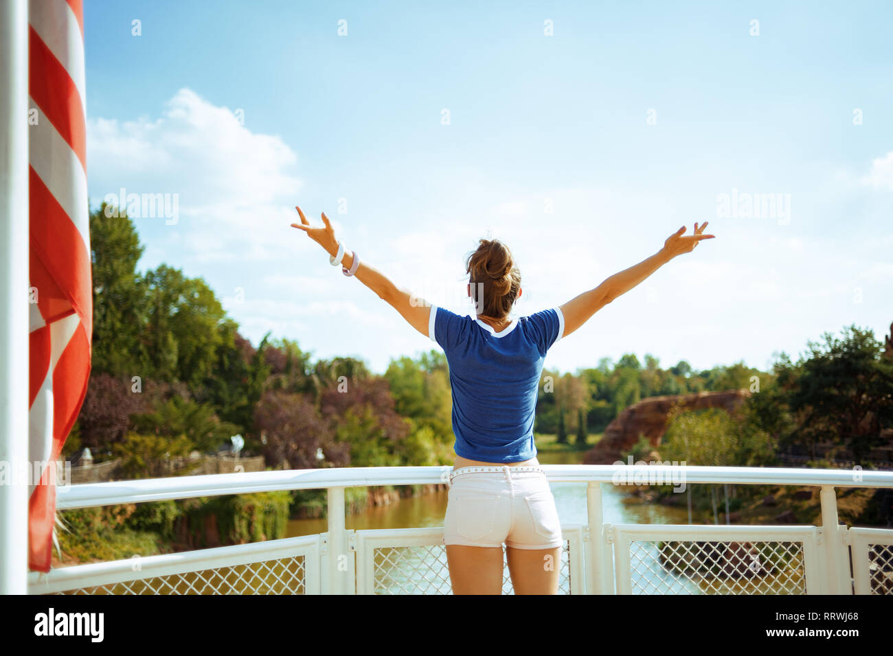 Seen from behind healthy tourist woman in blue t-shirt on river boat rejoicing while having river cruise. - Stock Image
