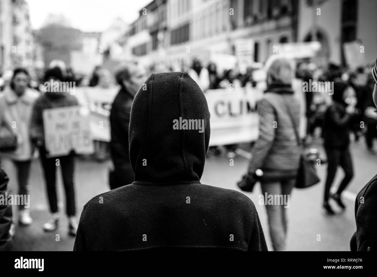 Silhouette looking at crowd marching in Central Strasbourg at the nationwide protest Marche Pour Le Climat black and white - Stock Image