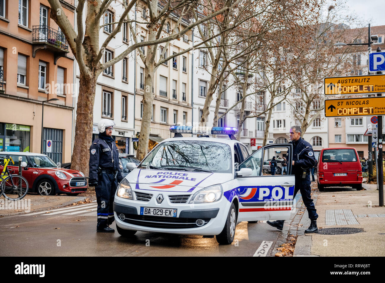STRASBOURG, FRANCE - DEC 8, 2018: Police officer securing the zone in front of crowd marching in Central Strasbourg at the nationwide protest demonstration Marche Pour Le Climat Stock Photo