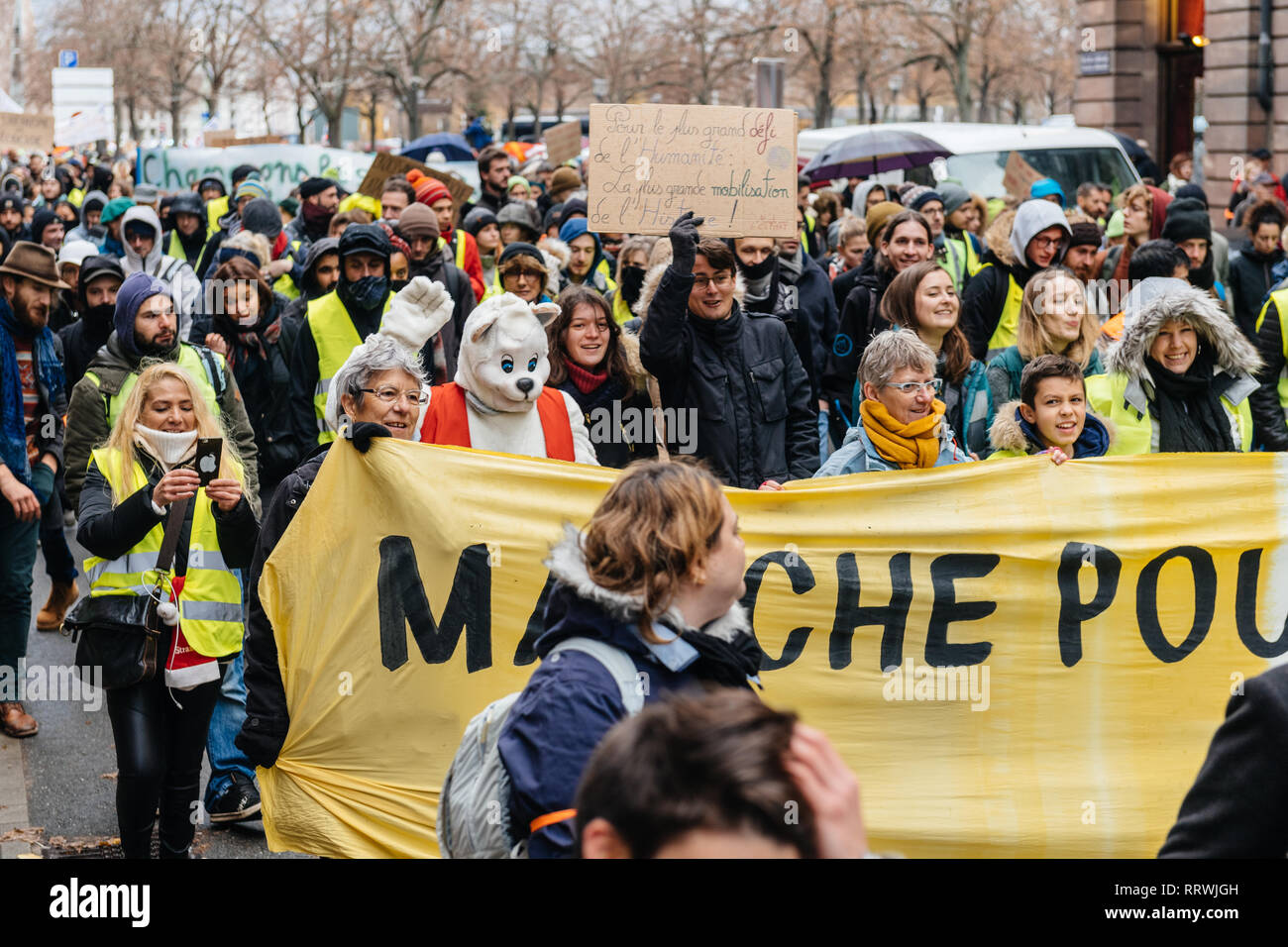 STRASBOURG, FRANCE - DEC 8, 2018: Crowd marching in Central Strasbourg at the nationwide protest Marche Pour Le Climat with large yellow palcard - Stock Image