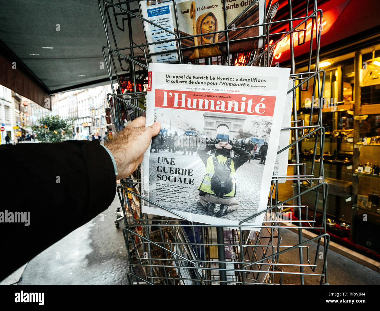 PARIS, FRANCE - DEC 10, 2018: Newspaper stand kiosk stand selling press with male hand buying latest l'Humanite edition featuring Gilets Jaunes Yellow Jackets movements on front cover - Stock Image
