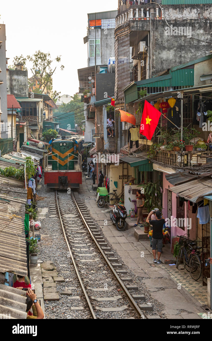 View of Hanoi train street between Le Duan and Kham Thin Street in Hanoi old quarter, Hanoi, Vietnam, Asia with a train travelling from Hanoi station - Stock Image