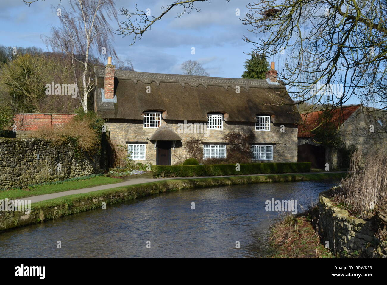 Thatched cottage by the river in Thornton Le Dale - North Yorkshire. Sunny day in February. Country Living. - Stock Image