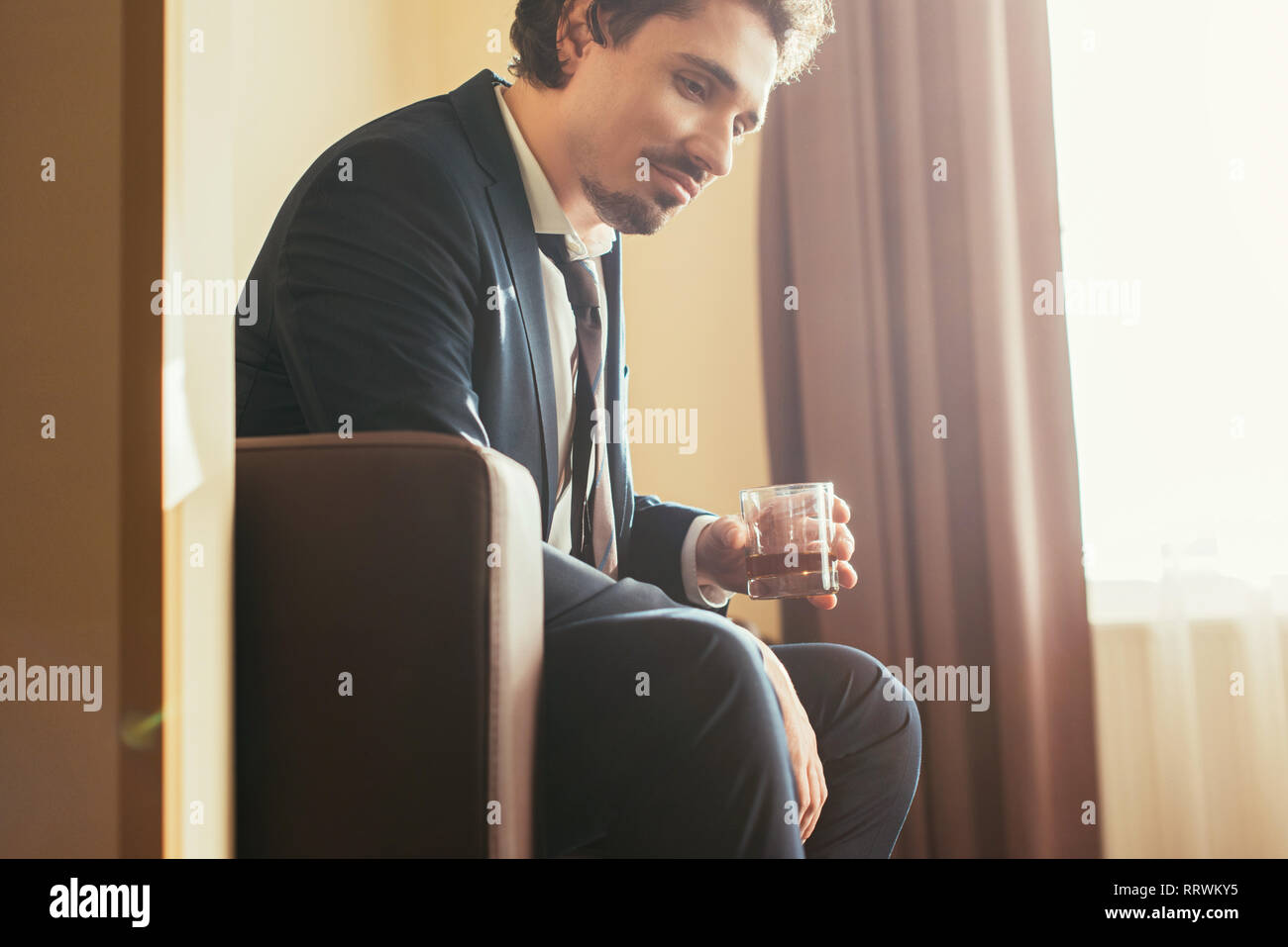 pensive businessman in formal wear holding glass of cognac in hotel room - Stock Image