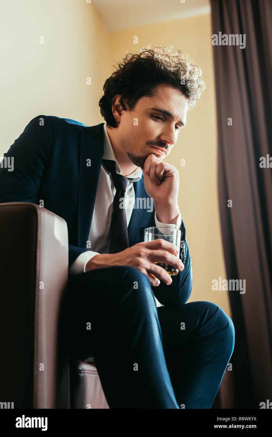 upset businessman in formal wear holding glass of whiskey in hotel room - Stock Image