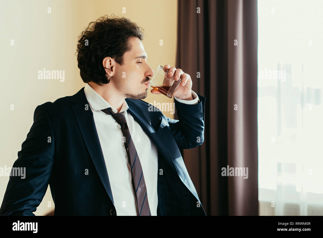 businessman in formal wear drinking whiskey from glass in hotel room - Stock Image