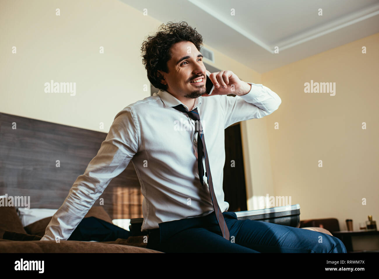 cheerful businessman in formal wear talking on smartphone in hotel room - Stock Image