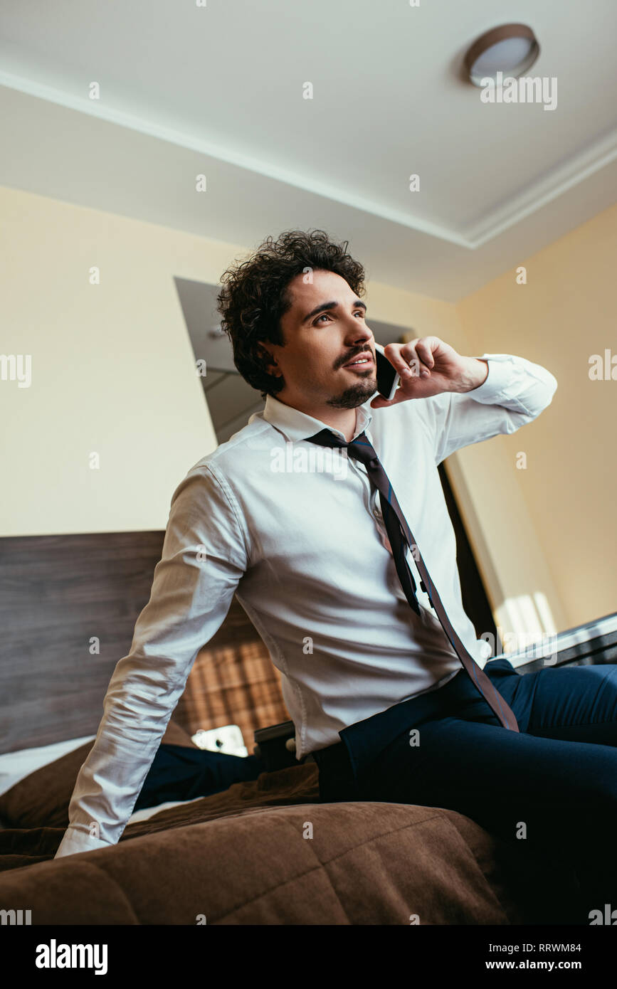 handsome businessman in formal wear talking on smartphone in hotel room - Stock Image