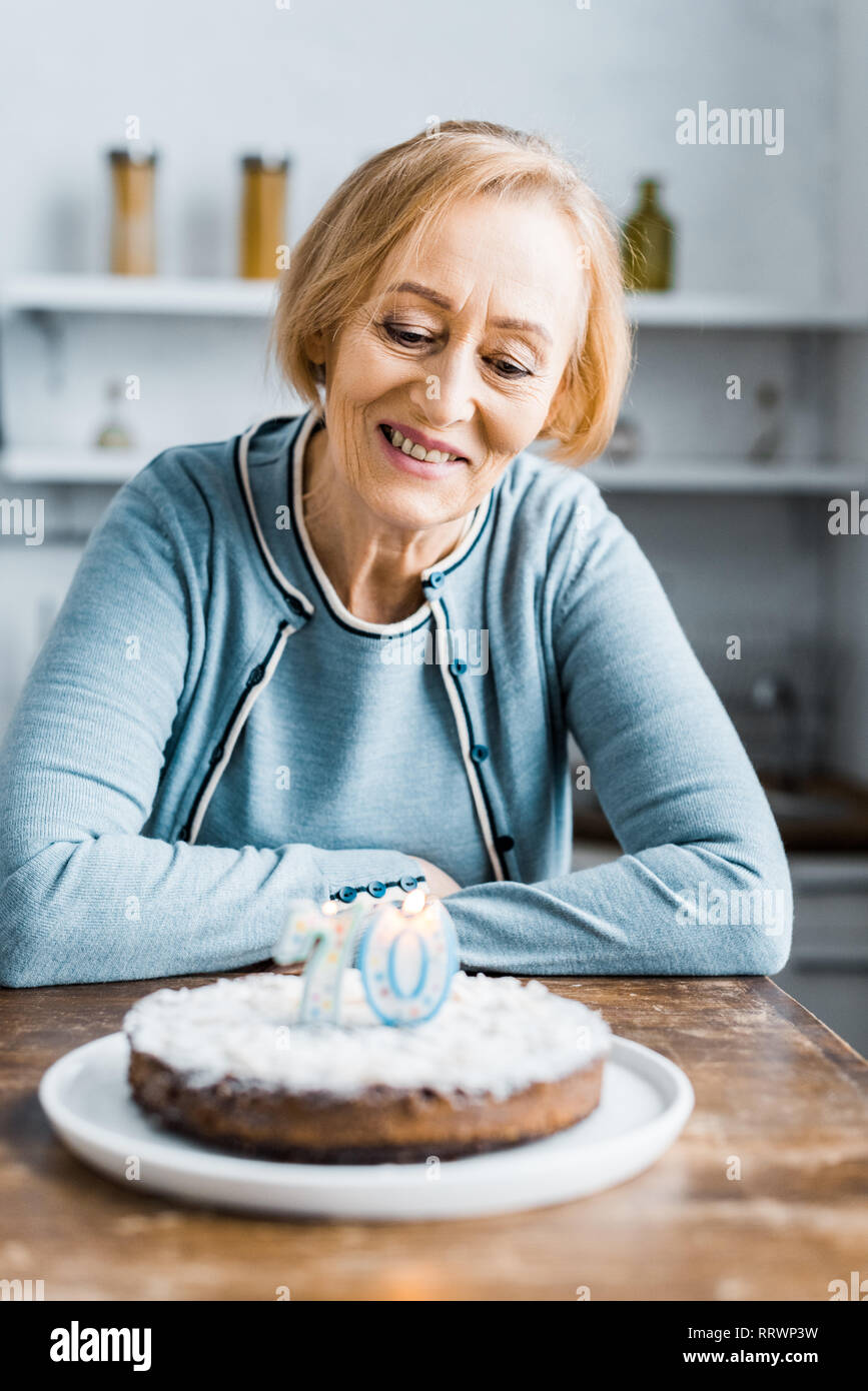 senior woman sitting at table and looking at cake with '70' sign during birthday celebration at home - Stock Image
