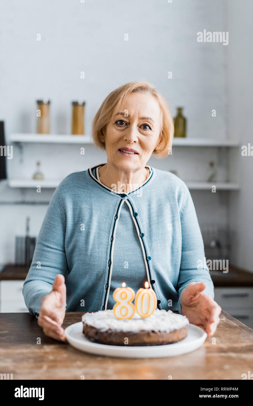 senior woman looking at camera and holding cake with '80' sign during birthday celebration at home - Stock Image
