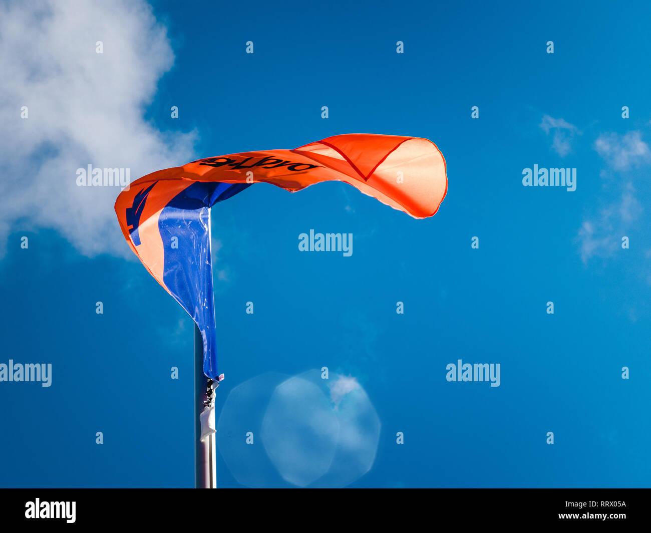 HAMBURG, GERMANY - MAR 20, 2018:  Hapag-Lloyd transnational German-based transportation company flag waving against blue sky - Stock Image