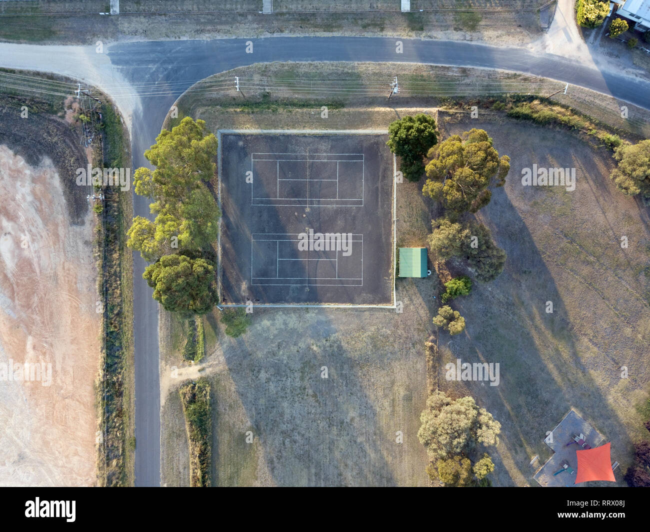 Tennis court aerial view empty of people in a small town Australia with country roads, trees and large expanse of paddocks and space. - Stock Image