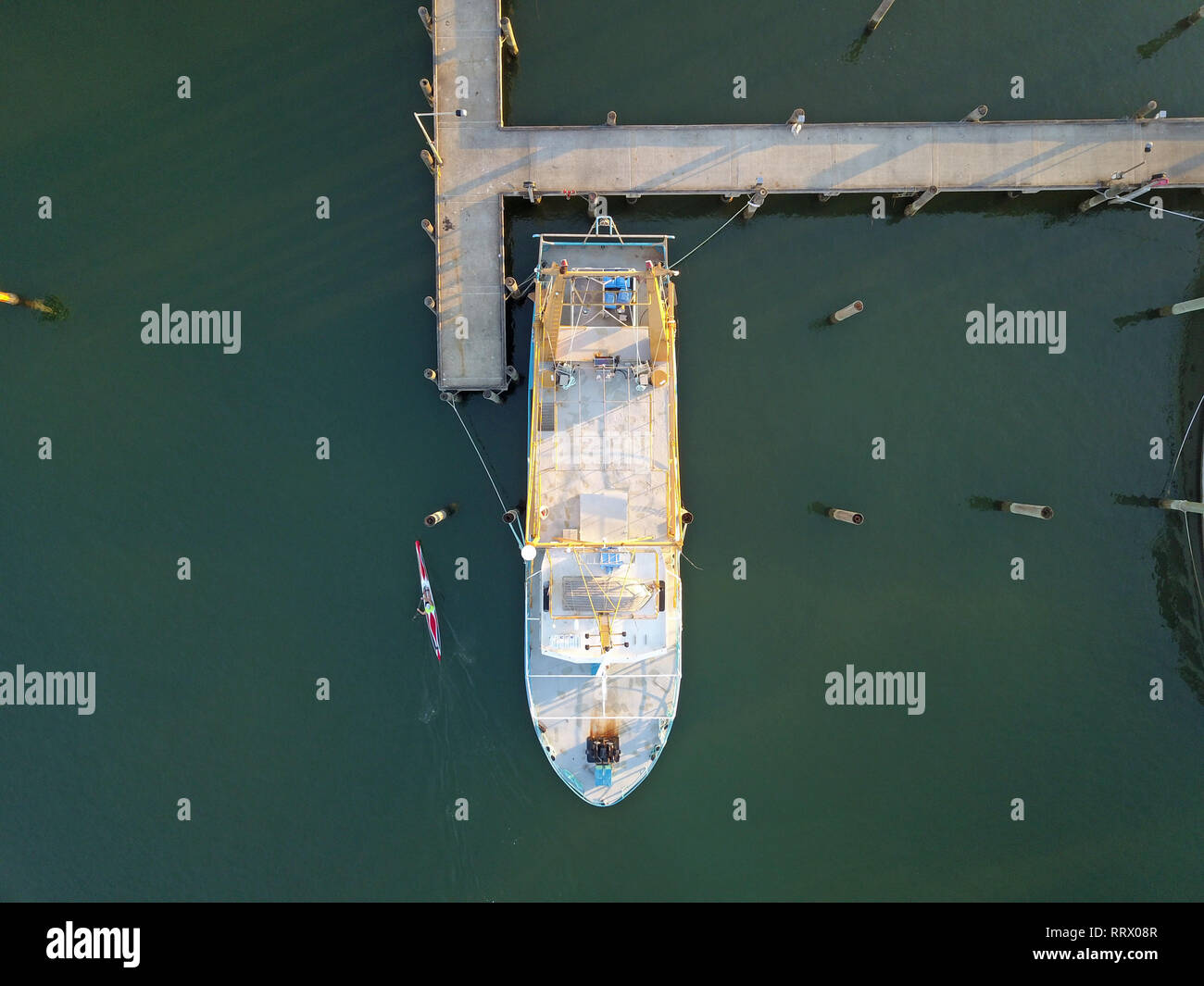 Fishing boat from above with nearby extreme kayaking ocean activity. Captured using aerial photography and remote drone in Queensland, Australia. - Stock Image