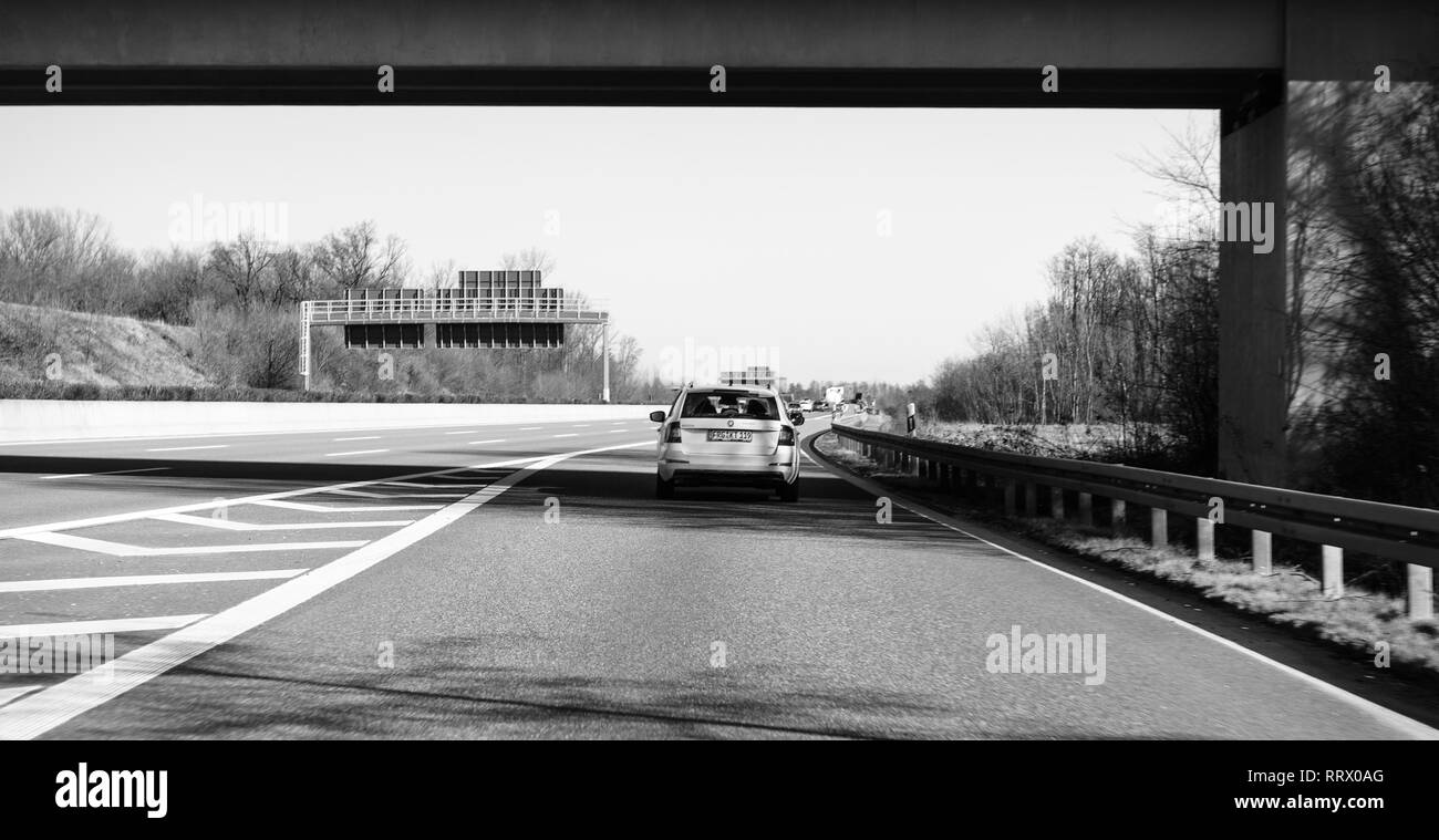 Germany - Feb 25, 2018: Wagon Skoda Octavia 4x4 car driving fast on winter day German Autobahn with the direction Offenburg, Basel, Frankfurt - black and white - Stock Image