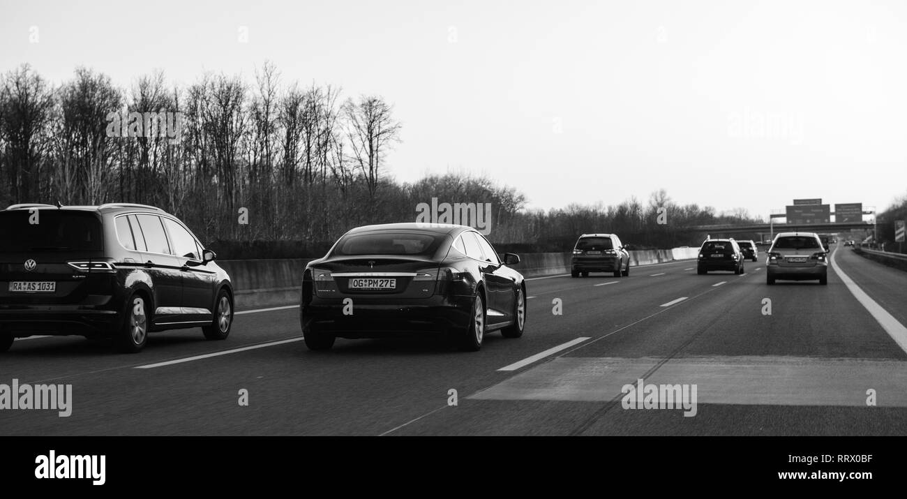 Germany - Feb 25, 2018: Luxury Tesla P85 and Multiple cars driving on the winter evening on the German Autobahn with the direction Offenburg, Basel, Frankfurt monochrome - Stock Image