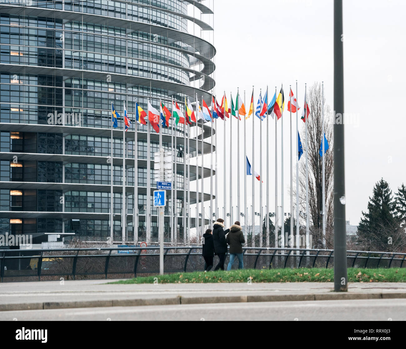 STRASBOURG, FRANCE - DEC 11, 2018: Pedestrians walking with European Union and French Flags flies at half-mast in front of the European Parliament following an attack in center of Strasbourg during annual Christmas Market - Stock Image