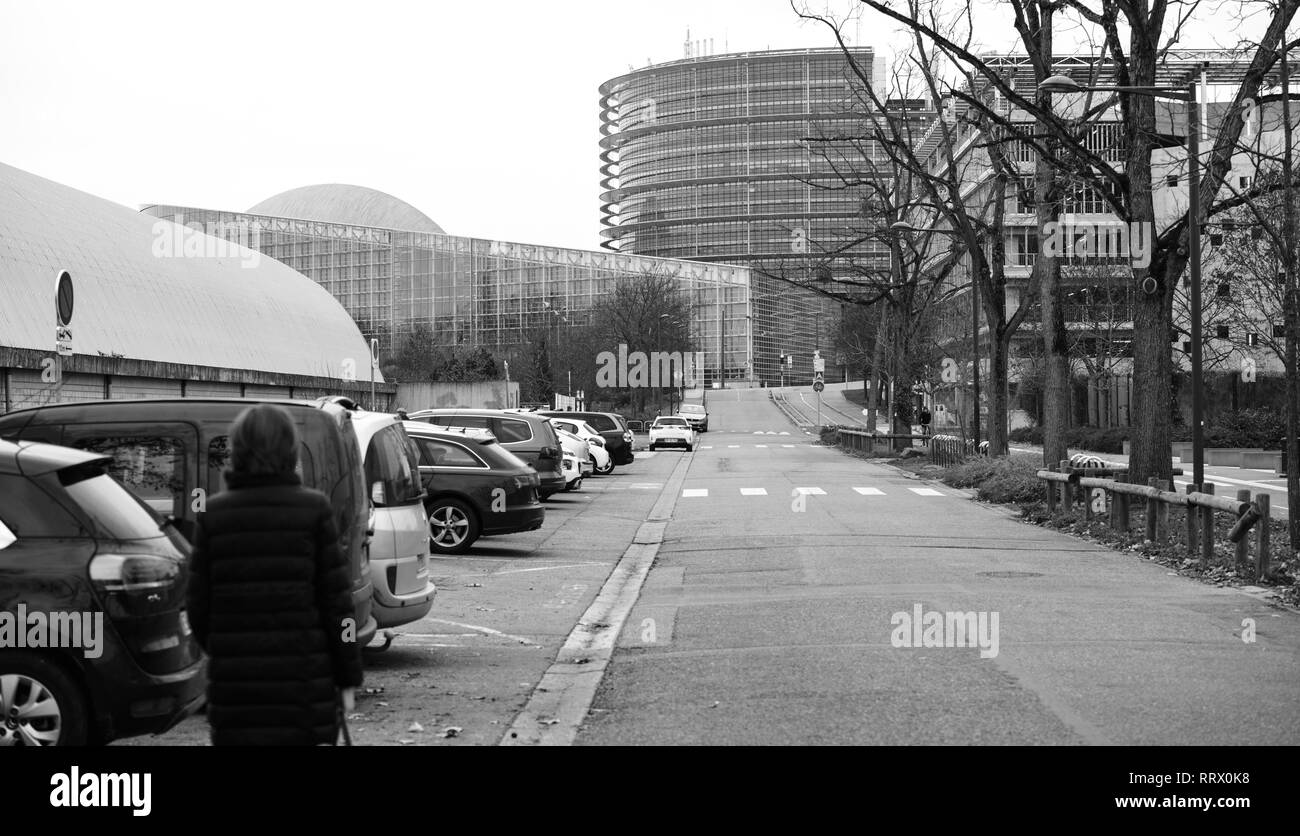 STRASBOURG, FRANCE - DEC 12, 2018: European Parliament building in Strasbourg with cars parked down the street and pedestrians walking - black and white - Stock Image