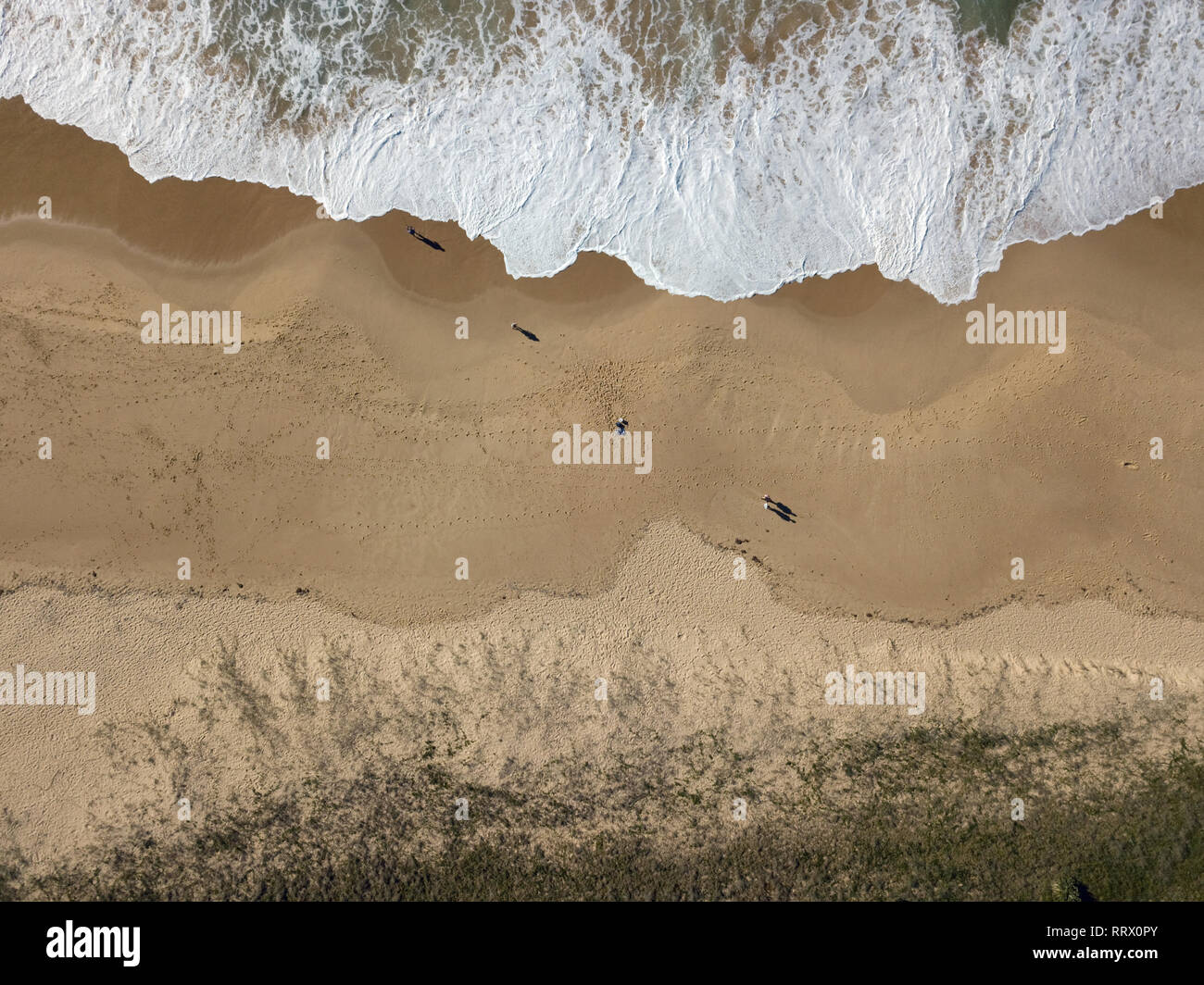 Australian beach and people landscape aerial view on sandy beach with waves and ocean crashing in. Bird's eye view captured with drone. - Stock Image