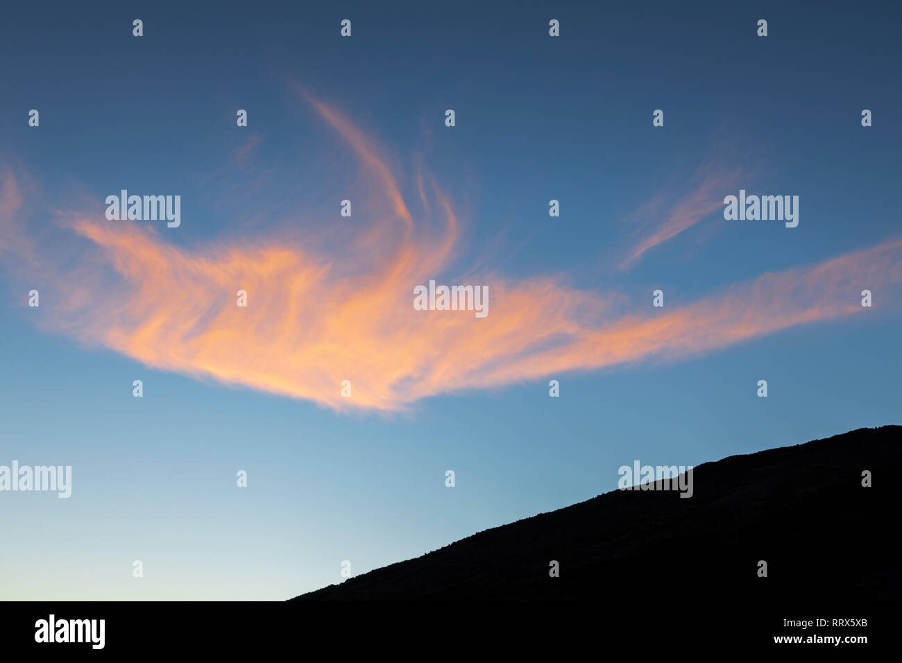 Wispy cloud lit orange by the setting sun in the Las Canadas del Teide national park, Tenerife, Canary Islands, Spain - Stock Image