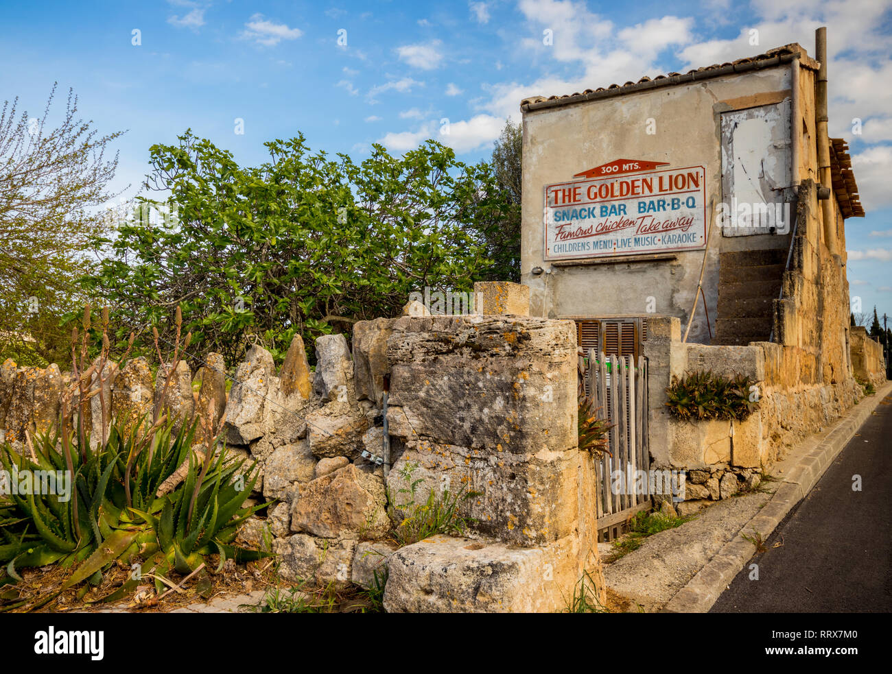 Old stone building advertising The Golden Lion snack bar, Alcudia, Mallorca (Majorca), Balearic Islands, Spain - Stock Image