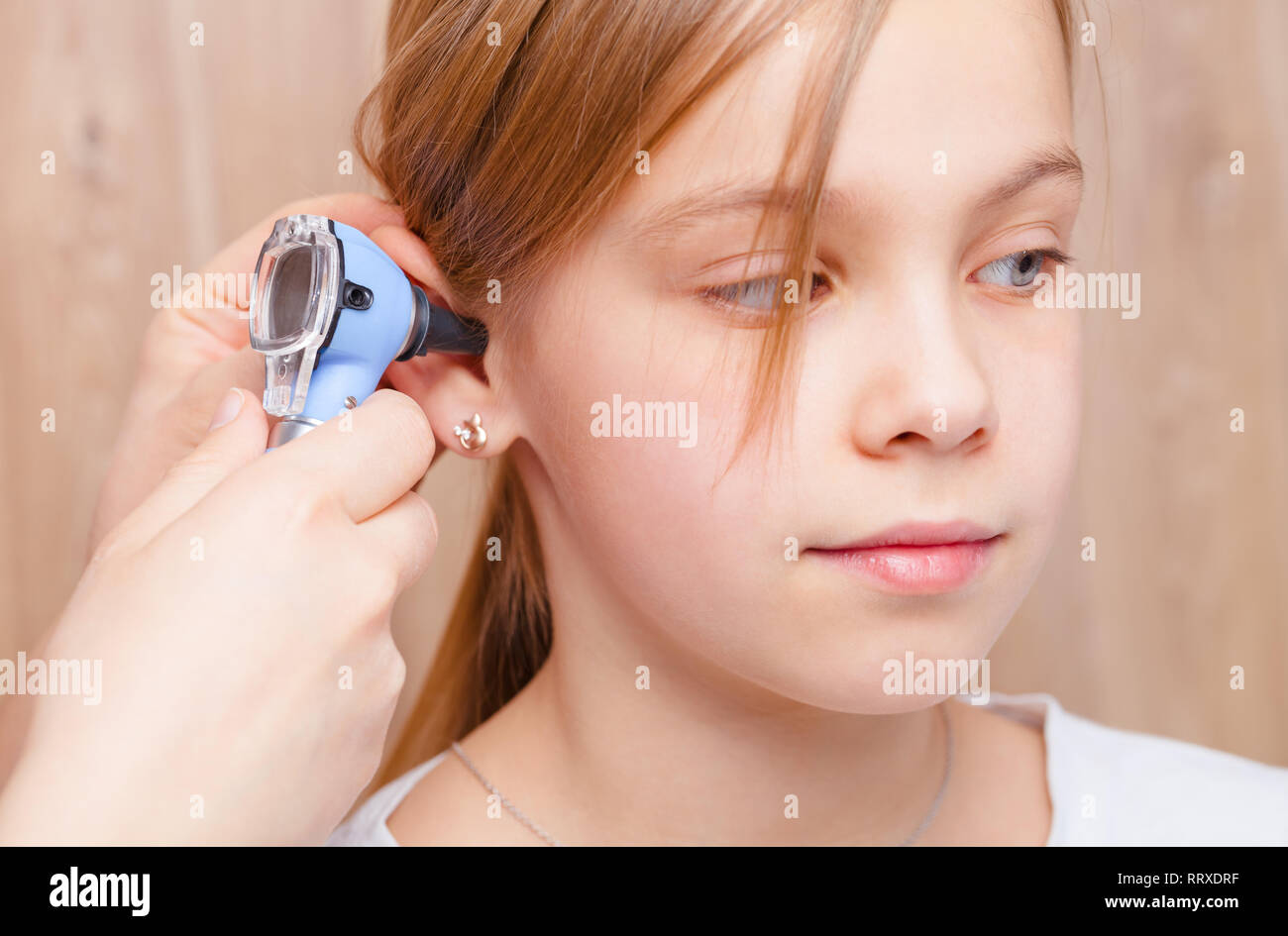 Female pediatrician examines elementary age girl's ear in pediatric clinic. Doctor using a otoscope or auriscope to check ear canal and eardrum membra Stock Photo