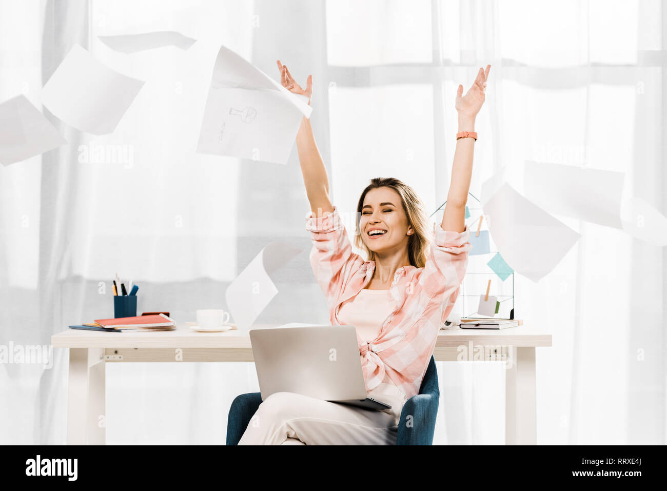 Laughing woman with laptop throwing out documents at workplace - Stock Image