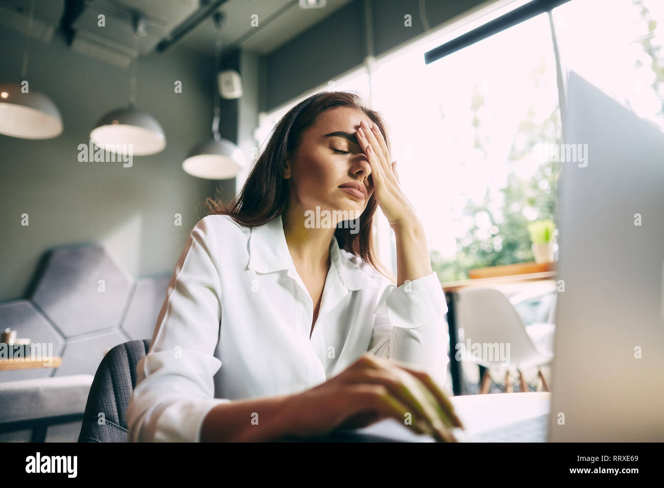 Attractive girl in white shirt working in cafe with gray laptop, online shopping concept, freelance work in progress, work from home, failed, sad emot - Stock Image