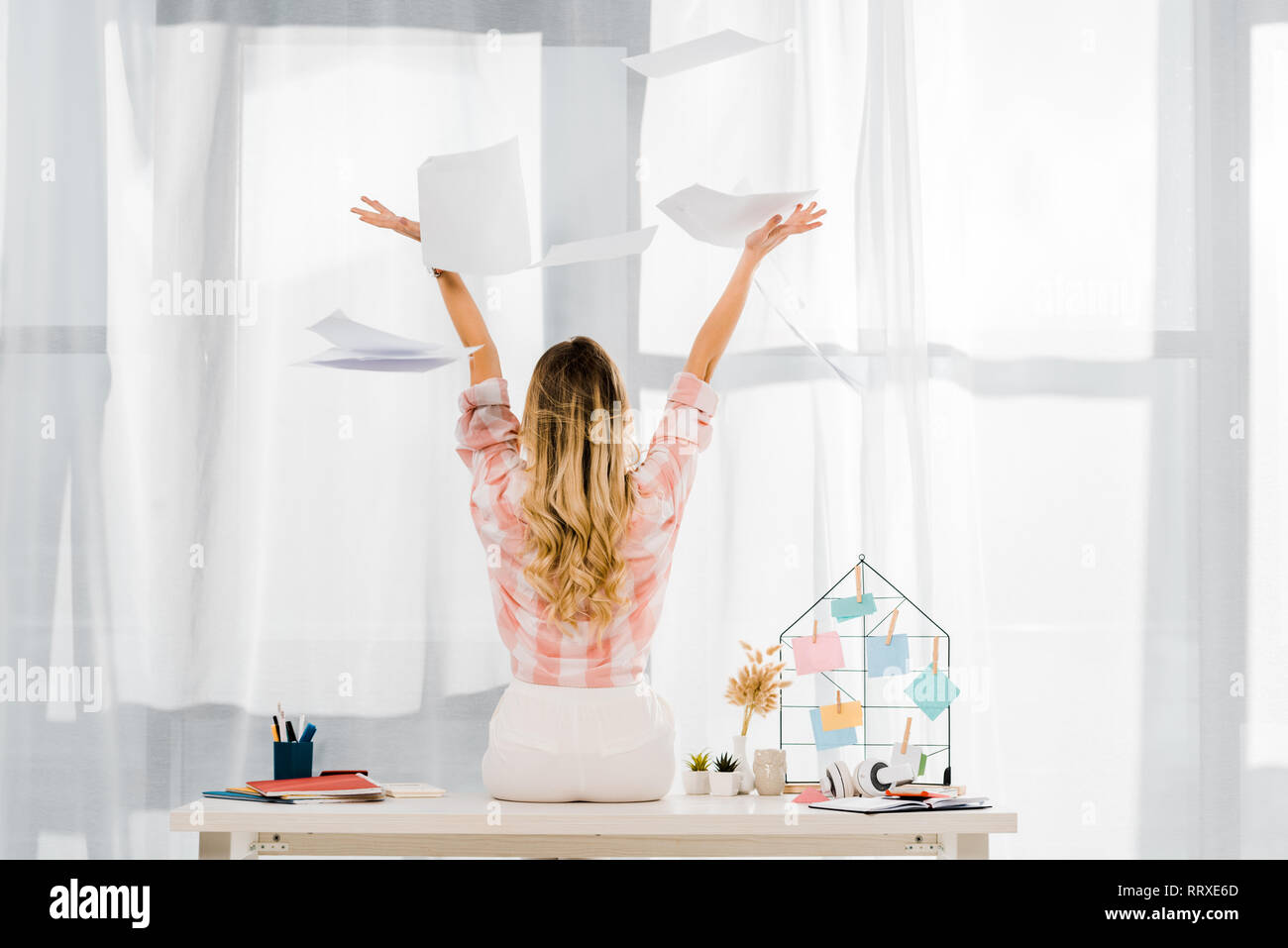 Back view of woman in checkered shirt sitting on table and throwing out documents - Stock Image