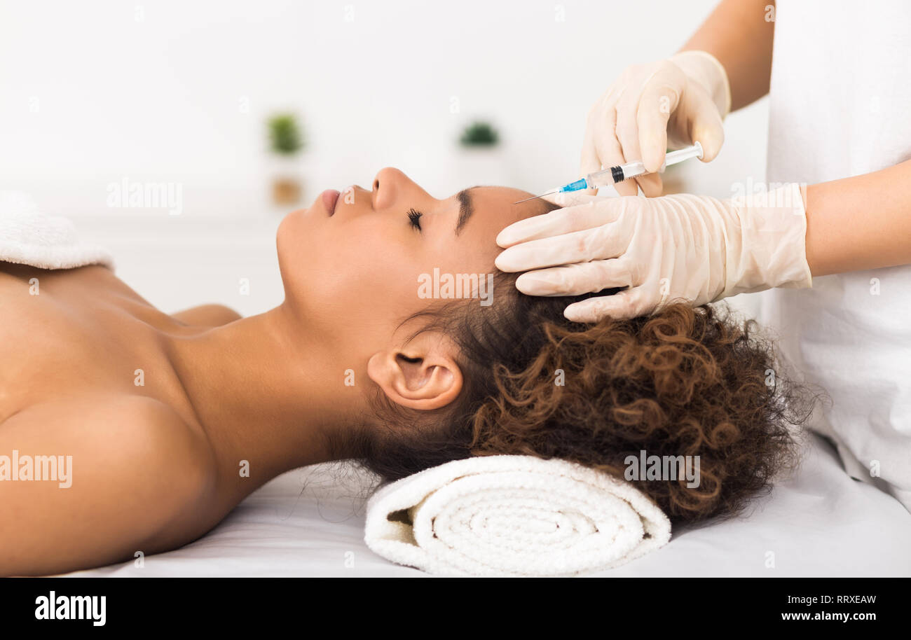 Aesthetic surgery. Woman having injection on forehead - Stock Image